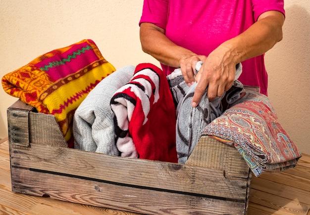 Een vrouw schikt de dekens in een container om ze op te bergen. een senior mensen. assortiment en verschillende kleuren. huishoudelijk werk concept
