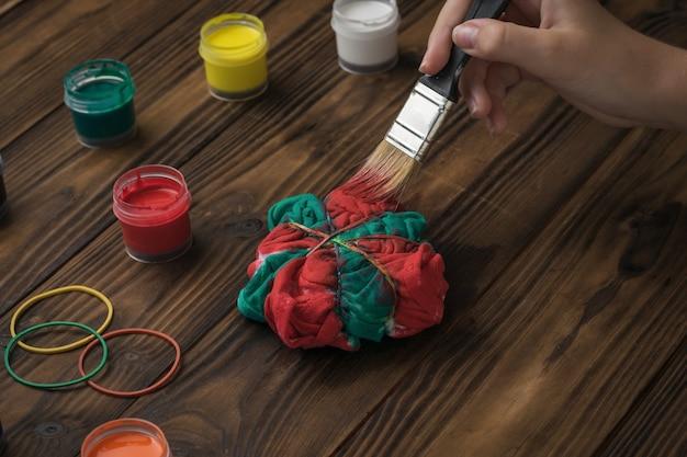 Een vrouw schildert haar ondergoed in tie-dye-stijl in rood en groen. stof beitsen in tie-dye-stijl.