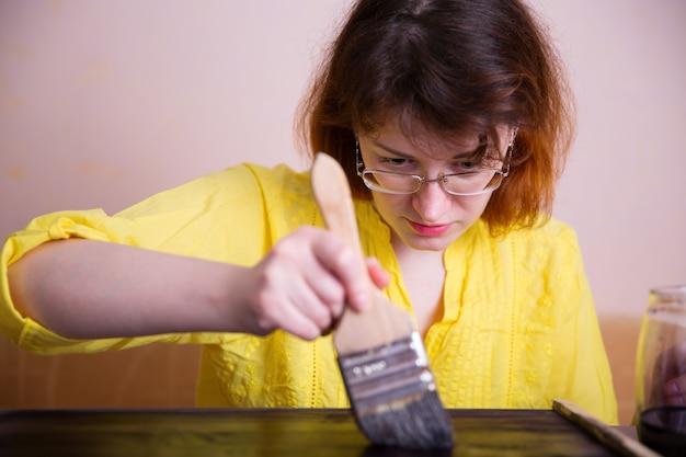 Een vrouw schildert het hout zorgvuldig in een donkere kleur