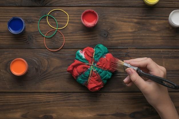 Een vrouw schildert kleding in stropdaskleurstof in rood en groen. stof beitsen in tie-dye-stijl.