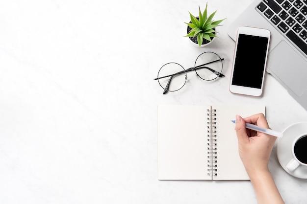 Een vrouw schrijft notities die op een gestileerd marmeren bureau worden geïsoleerd