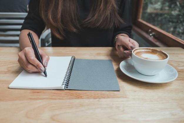 Een vrouw schrijft op een notitieblok terwijl het drinken van koffie op houten tafel