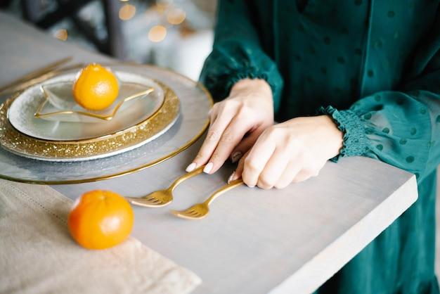 Een vrouw serveert een feestelijke tafel. gouden vorken en borden, mandarijnen