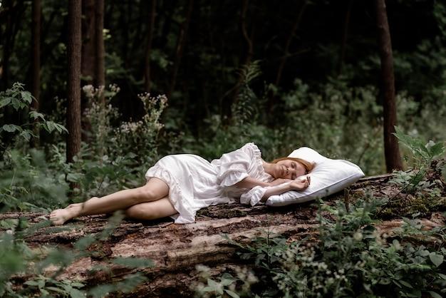 Een vrouw slaapt in het bos op een kussen. gezond, gezond slaapconcept. rust, ontspanning in de natuur.