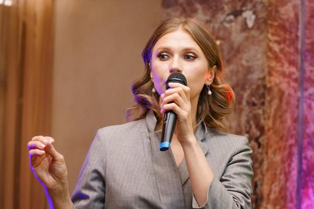 Een vrouw spreekt in een microfoon, geeft een lezing over zaken. conferentie training seminar zakelijke presentatie publieksvergadering.