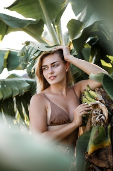 Een vrouw staat in de buurt van groene bananenbladeren op het eiland. tropische bomen