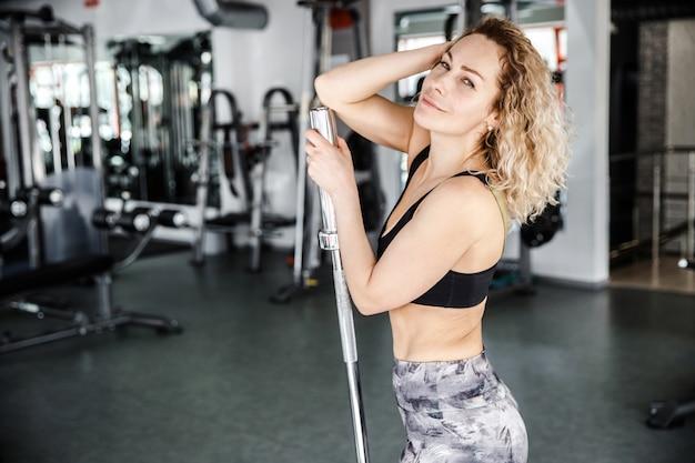 Een vrouw staat in een lichte sportschool. haar hand is op een halter. ze kijkt naar de camera en lacht.
