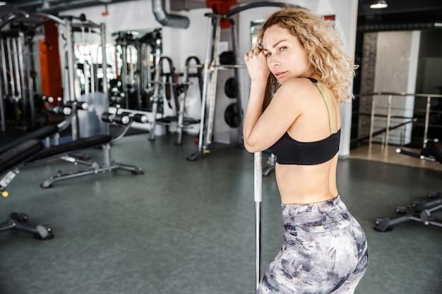 Een vrouw staat in een lichte sportschool. haar handen zijn op een halter. ze kijkt naar de camera.