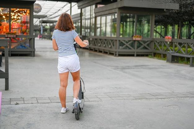 Een vrouw staat met een scooter op de dijk van kazan. milieuvriendelijk vervoer.