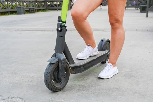 Een vrouw staat met een scooter op de kade van kazan. milieuvriendelijk vervoer.