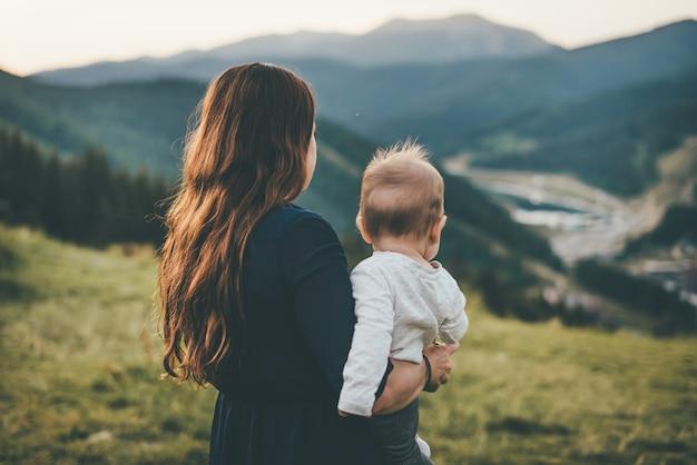 Een vrouw staat naar de bergen te kijken en houdt een kind in haar armen