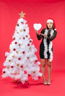 Een vrouw staat naast de kerstboom