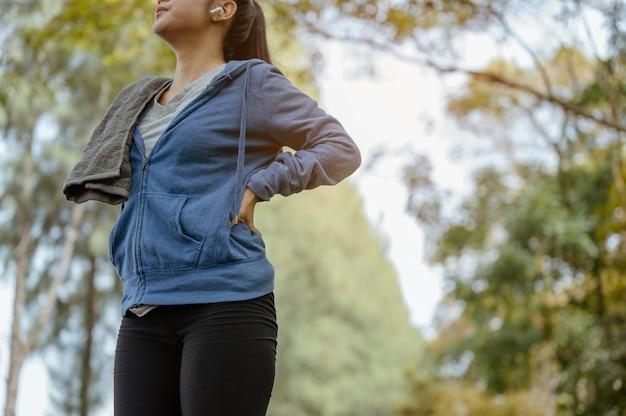 Een vrouw staat om natuurlijke lucht in te ademen na het joggen. natuurpark. gezond en levensstijlconcept.