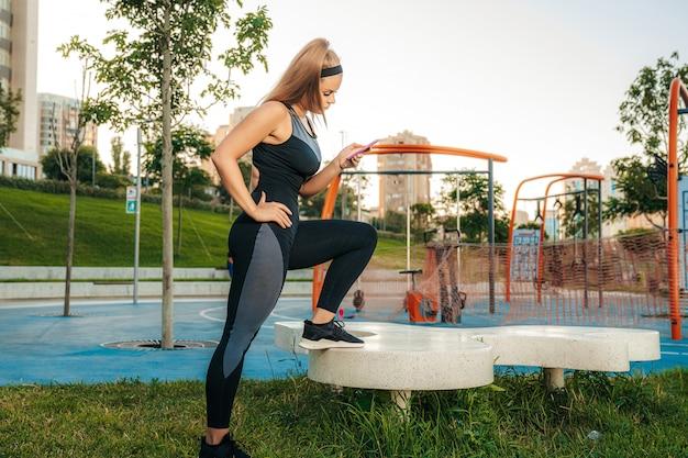 Een vrouw staat op de sportschool buiten met een telefoon