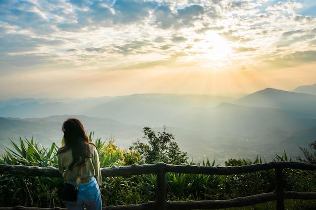 Een vrouw staat te kijken naar het uitzicht en de zon opkomen in de ochtendhemel.