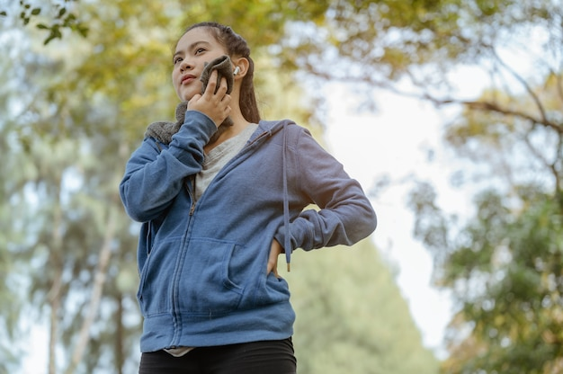 Een vrouw stond om te rusten en veegde het zweet weg nadat het joggen klaar was natuurpark gezond