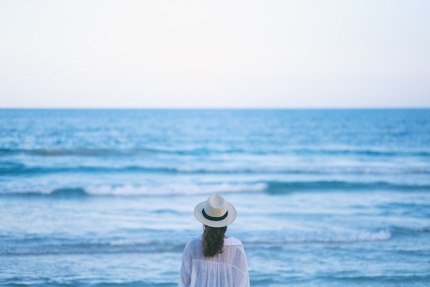 Een vrouw stond op het strand, alleen kijkend naar een prachtige zee en de blauwe lucht