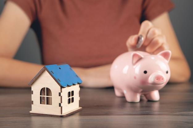 Een vrouw stopt een munt in een spaarvarken en naast een huis