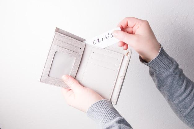 Een vrouw stopt een papier met de inscriptie crisis in een portefeuille