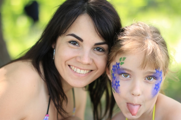 Een vrouw tekent op het gezicht van een meisje
