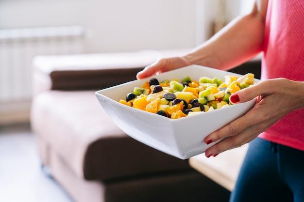 Een vrouw thuis draagt een fruitsalade in een witte kom op een houten tafel