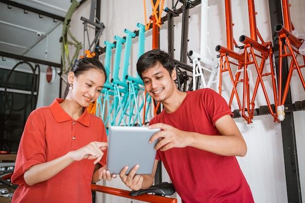 Een vrouw toont haar tablet aan een mannelijke winkelbediende tijdens het chatten