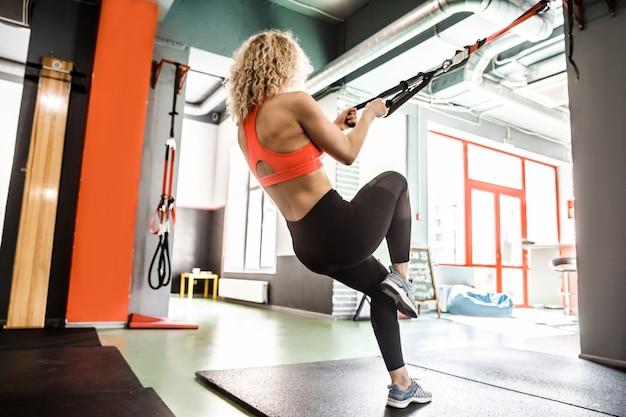 Een vrouw traint met een elastiekje in een sportschool, ze leunt achterover.
