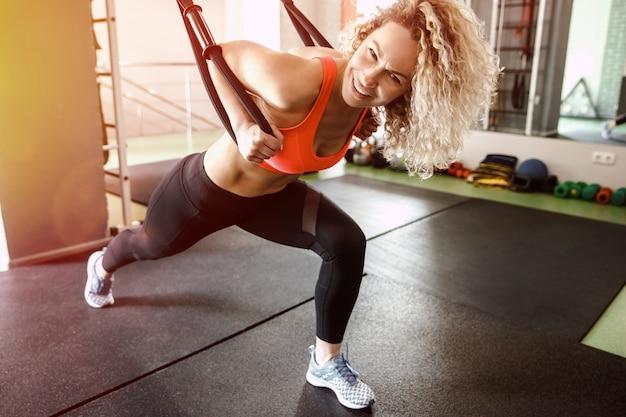 Een vrouw traint met elastiekjes. ze kijkt naar de camera.