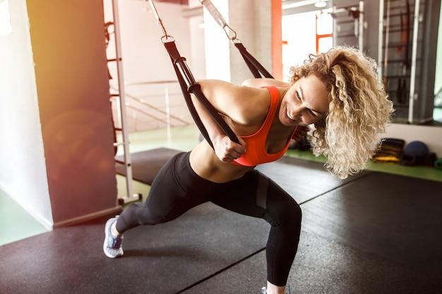 Een vrouw traint met elastiekjes. ze kijkt weg en glimlacht.