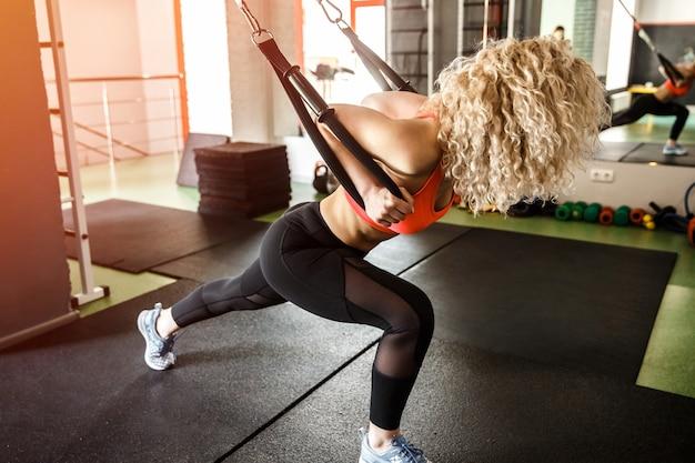 Een vrouw traint met elastiekjes, ze leunt naar voren.