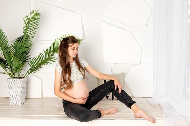 Een vrouw van 8-9 maanden zwanger zit voor het raam in een lichte kamer
