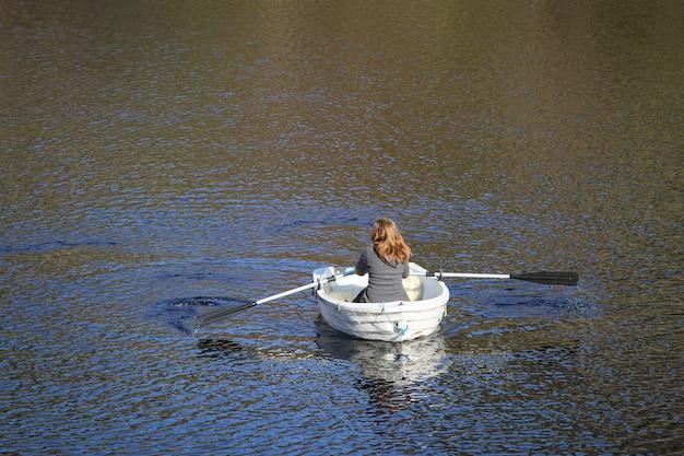 Een vrouw, van achteren gezien, roeit op een zonnige dag een kleine witte boot