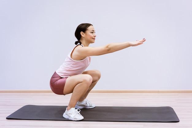 Een vrouw van blanke etniciteit in sportkleding is thuis bezig met fitness tegen de achtergrond van een muur. gezonde levensstijl en slank lichaamsconcept