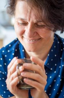 Een vrouw van middelbare leeftijd in het café heeft een kop hete thee in haar handen