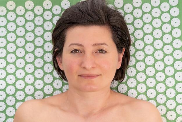 Een vrouw van middelbare leeftijd masseert rug, lichaam en ruggengraat op een acupunctuurkleed.
