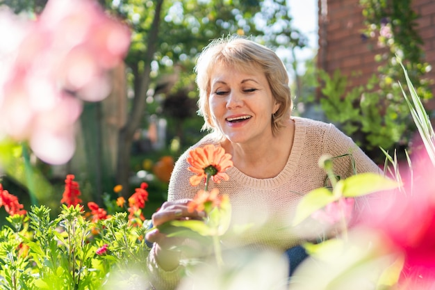 Een vrouw van middelbare leeftijd zorgt voor de planten