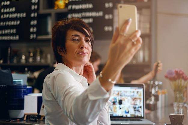 Een vrouw van veertig jaar schrijft de vlog in de telefoon terwijl ze aan de bar in een café zit
