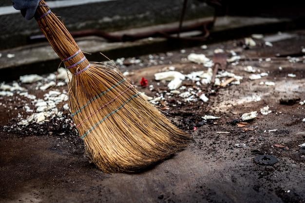 Een vrouw veegt het vuilnis schoon. het gebied schoonmaken van vuilnis in de tuin buiten.