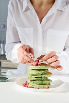 Een vrouw verfraait spirulina-pannenkoeken met bessen.