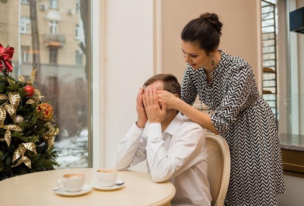 Een vrouw verrast een man in een café