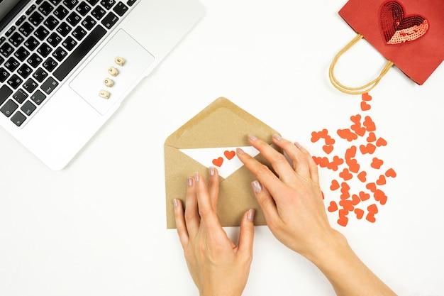 Een vrouw versiert een bruine envelop met rode harten voor valentijnsdag