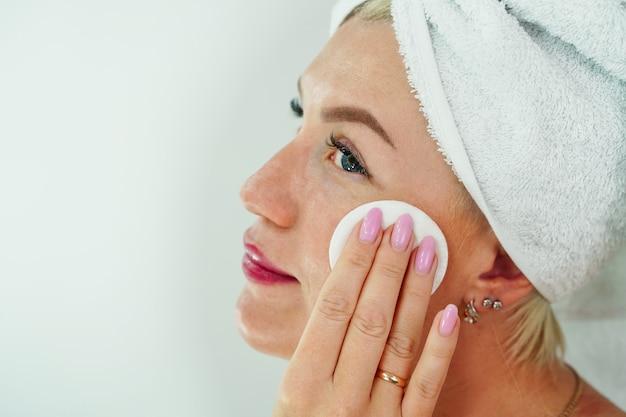 Een vrouw verwijdert make-up met een servet in de badkamer veegt haar gezicht af met een wattenschijfje en reinigt ...