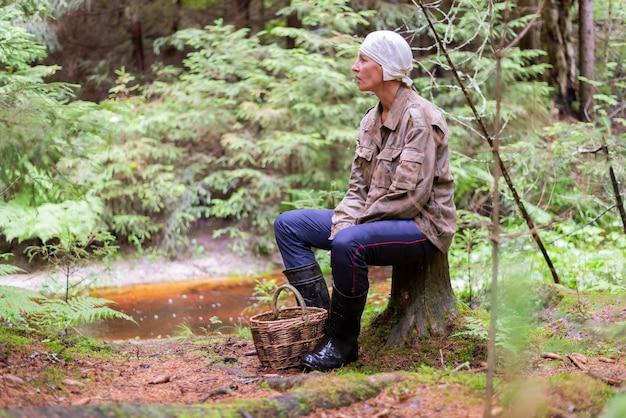 Een vrouw verzamelt paddenstoelen in het bos, met een mand. voor elk doel.
