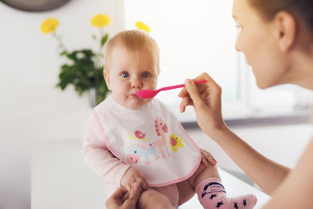 Een vrouw voedt een baby met een lepel.
