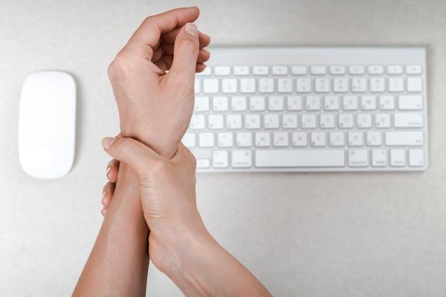 Een vrouw voelt pijn in haar pols met behulp van haar computermuis.