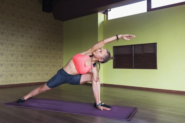 Een vrouw voert de vira bhadrasana-oefening krijger pose 1 uit, staat op een mat in de studio