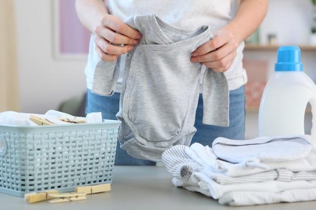 Een vrouw vouwt schone en frisse babykleertjes en wast babykleertjes