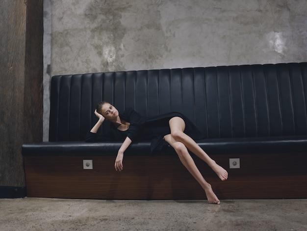 Een vrouw wacht op een vlucht in een vliegtuig liggend op een bank in een donkere kamer