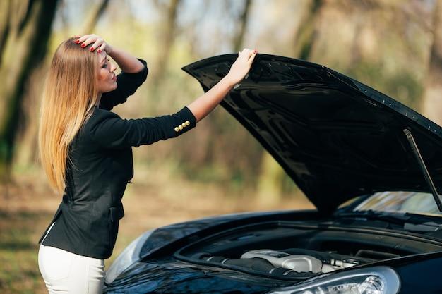 Een vrouw wacht op hulp in de buurt van haar auto met pech langs de weg.