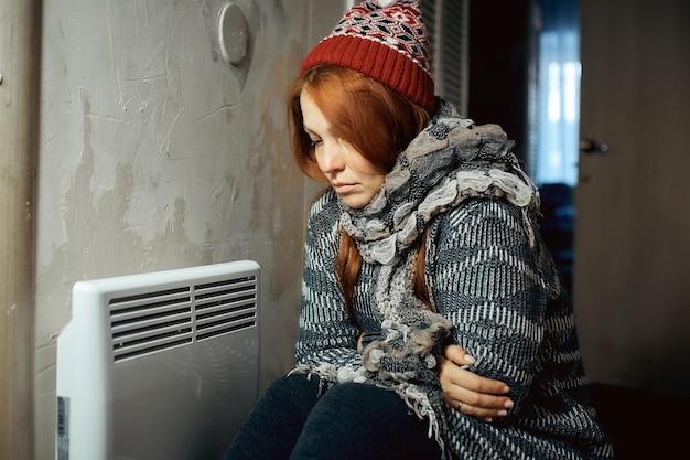 Een vrouw warmt zichzelf op aan de radiator in een koud huis, problemen met verwarming, verwarming van de kamer met een elektrische convector